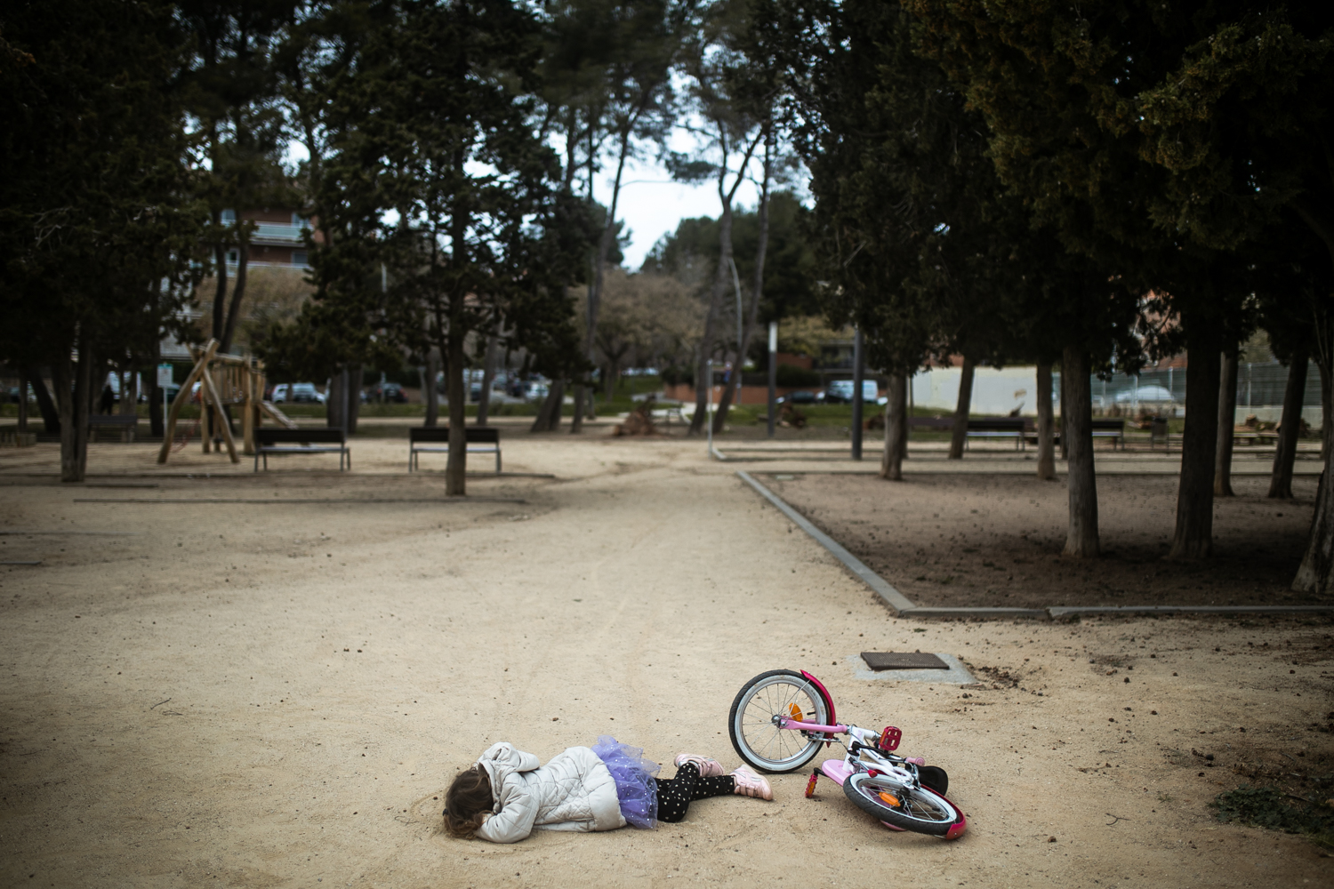 a small girl is lying on the floor in castelldefels